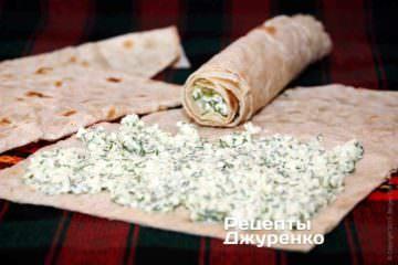 На лаваш розміром трохи більше долоні покласти столову ложку сиру