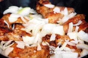 Добавить нарезанный лук на сковородку к кускам курицы