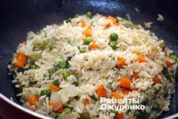 Когда вода вся практически впиталась рисом, с помощью лопатки выложить рис горкой, сгребая его от стенок к центру. Дать пропариться под крышкой
