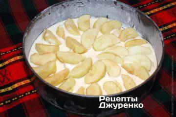 Поверх теста разложить остатки яблок