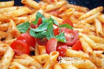 Змішати пасту з нарізаними помідорами чері та базиліком