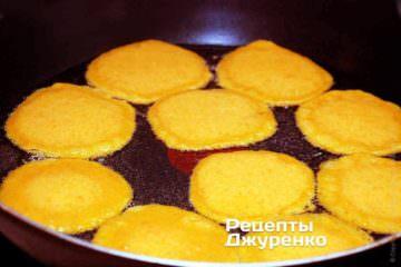 Звичайною ложкою викладати порції гарбузової суміші на сковорідку