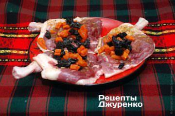 Разложить нарезанные курагу и чернослив равными частями на утиное мясо