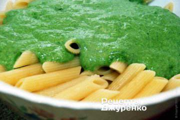 Переложить пасту в глубокую миску и смешать со соусом из шпината