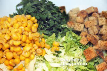 Добавить в салат сухарики, зелень и кукурузу