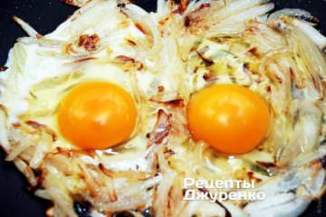 Вылить содержимое яйца на лук