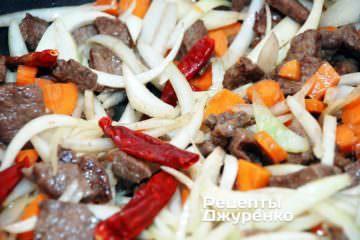 Добавить лук к мясу и продолжать жарить