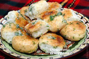 Готовые пампушки остудить под тканью, разделить на отдельные кусочки, и, обмакивая со всех сторон в чесночный соус, выложить на блюдо