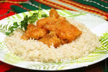 На тарелку выложить рис и рыбу в соусе