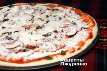 Густо посыпать пиццу пармезаном