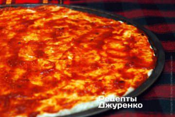 Смазать тесто для пиццы томатным соусом
