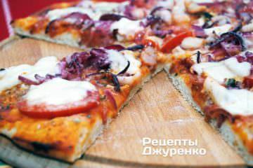 Готовую пиццу коктейль с морепродуктами и моцареллой разрезать специальным ножом на 6-8 частей