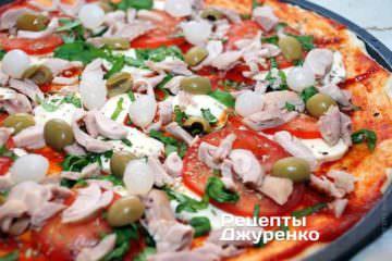 Розкласти на піцу мариновану цибуля і оливки