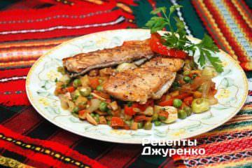 На тарелки выложить овощи и рыбу