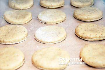Разложить печенье на бумаге для выпечки
