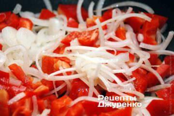 Красный сладкий перец очистить от семян и нарезать достаточно крупными ломтиками. На сковородку влить 2 ст.л. оливкового масла и поджарить лук и перец на самом маленьком огне до мягкости