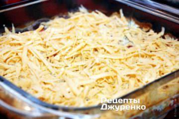 Затем блюдо извлечь из духовки и посыпать натертым на мелкую терку твердым сыром