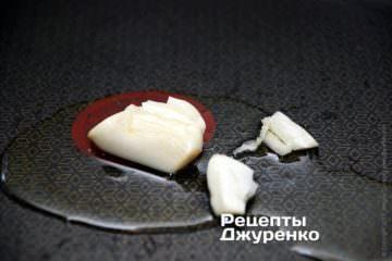 У сковороді, на розігрітій оливковій олії обсмажити два очищених і розчавлених зубчиків часнику
