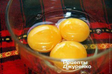 В глубокую мисочку выпустить содержимое одного яйца и добавить два желтка
