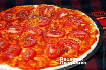 На тісто викласти нарізаний помідор