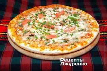 Украсить пиццу ломтиками рыбы и зеленью