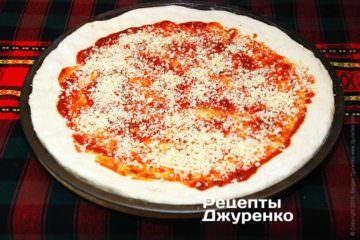 Посипати піцу половиною емменталя і орегано