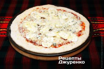 Посипати всю піцу тертим пармезаном і залишками емменталя