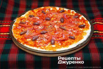 Розкласти нарізаний помідор і оливки