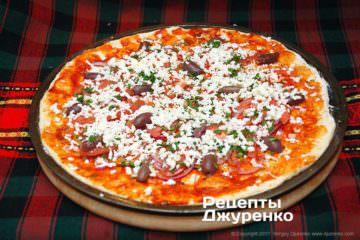Посипати піцу більшлю частиною натертої на терку моцарелли