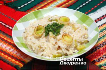 Выложить рис на тарелки, посыпать зеленью и пармезаном