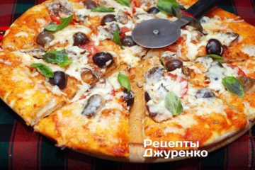 Разрезать пиццу с сардинами