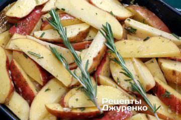 Перекласти підготовлену картоплю в деко. Покласти зверху залишилася гілочку розмарину