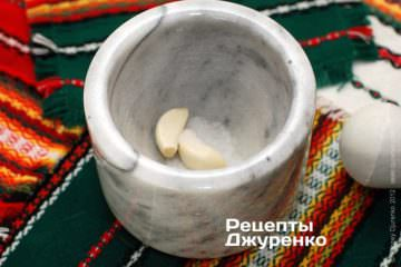 Розтерти часник з сіллю і додати оливкову олію