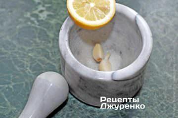 Растереть чеснок с солью и лимонным соком