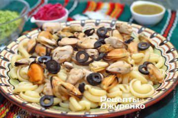 Выложить нарезанные колечками черные оливки