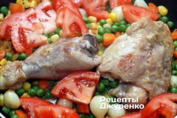 Помідор нарізати тонкими пластинками і викласти поверх курки і овочів