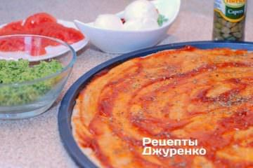 Смазать тесто соусом и посыпать орегано