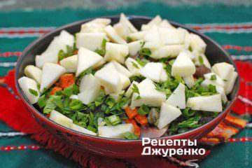 Добавить в салат яблоко и зелень, полить заправкой