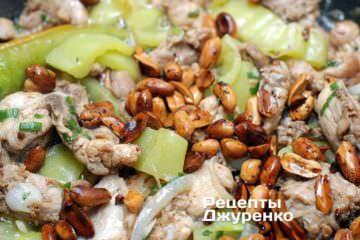 Добавить обжаренный арахис, влить соус и перемешать