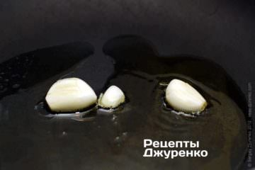 На масле быстро обжарить слегка расплющенные зубчики чеснока