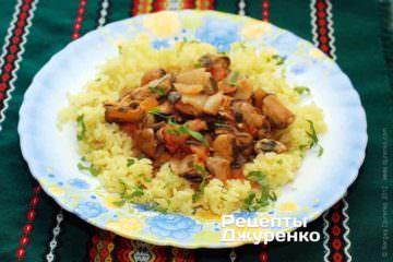 Выложить на тарелку рис и соус с мидиями