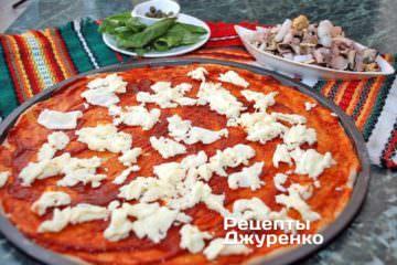 Поверх томатного соуса натереть моцареллу