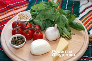 Ингредиенты: тесто для пиццы, зеленый базилик, чеснок, кедровые орешки, оливковое масло, помидоры, моцарелла, каперсы, специи