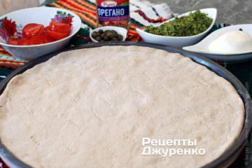 Готовое тесто раскатать, и выложить на смазанную оливковым маслом форму для пиццы