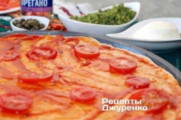 Розкласти помідори і посипати орегано