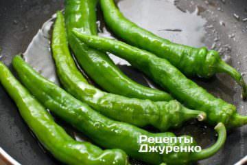 Выложить острые перцы на сковородку, и жарить
