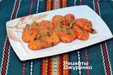 Выложить креветки на тарелку и полить соусом