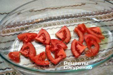 Смазать форму для запекания маслом и выложить немного нарезанного помидора
