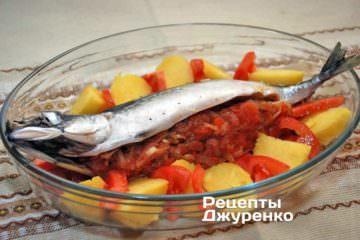 Навколо риби укласти печену картоплю і помідори