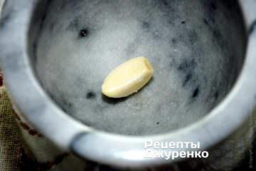 У ступці розтерти очищений часник, щіпку солі і чорного меленого перцю